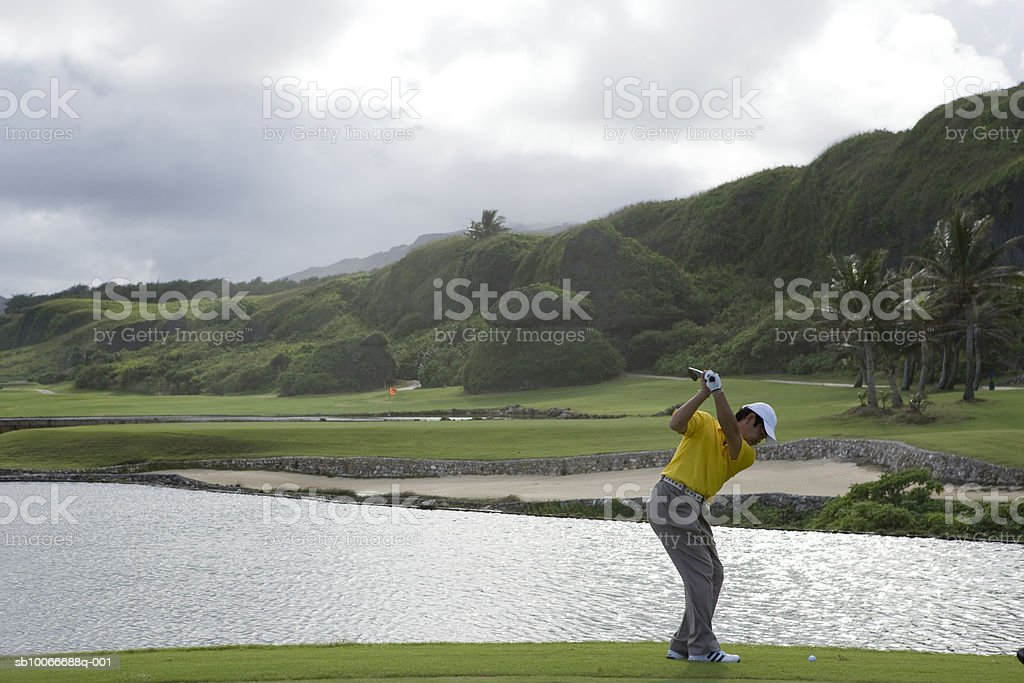 Mature man swinging golf club royalty-free stock photo