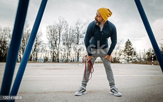 Mature bearded man taking a break after exercising with resistance band outdoors