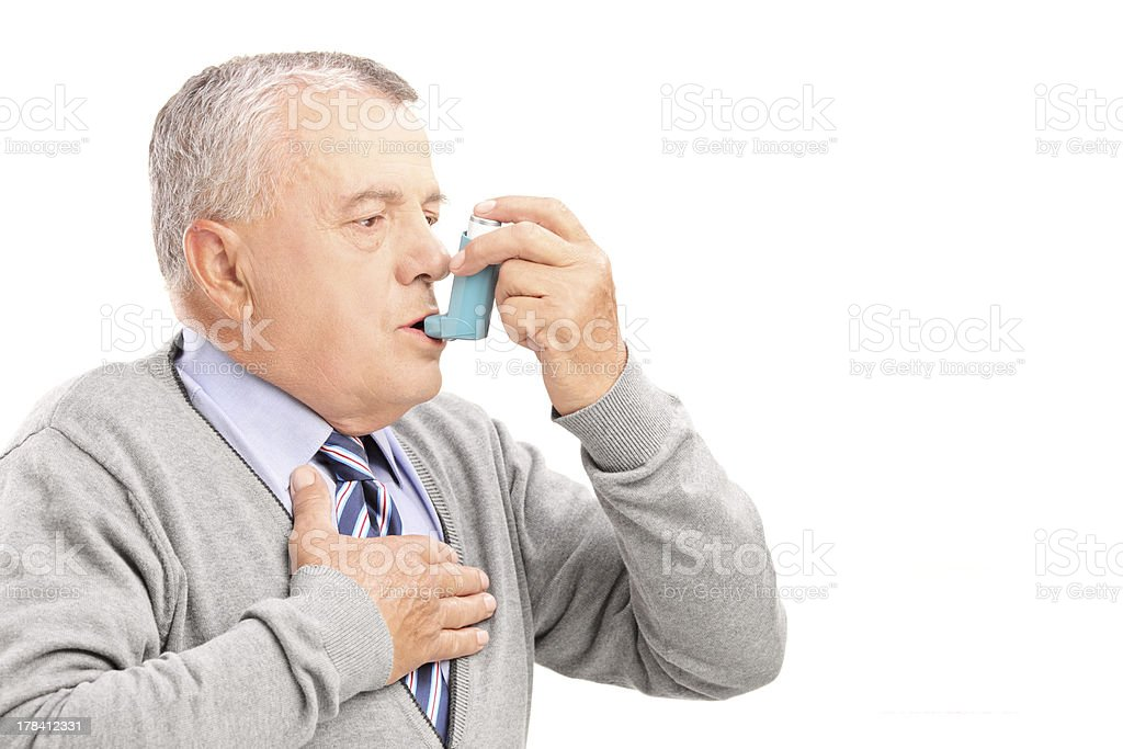 Mature man taking asthma treatment stock photo