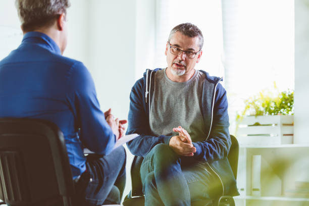 Mature man talking with psychotherapist in his office stock photo