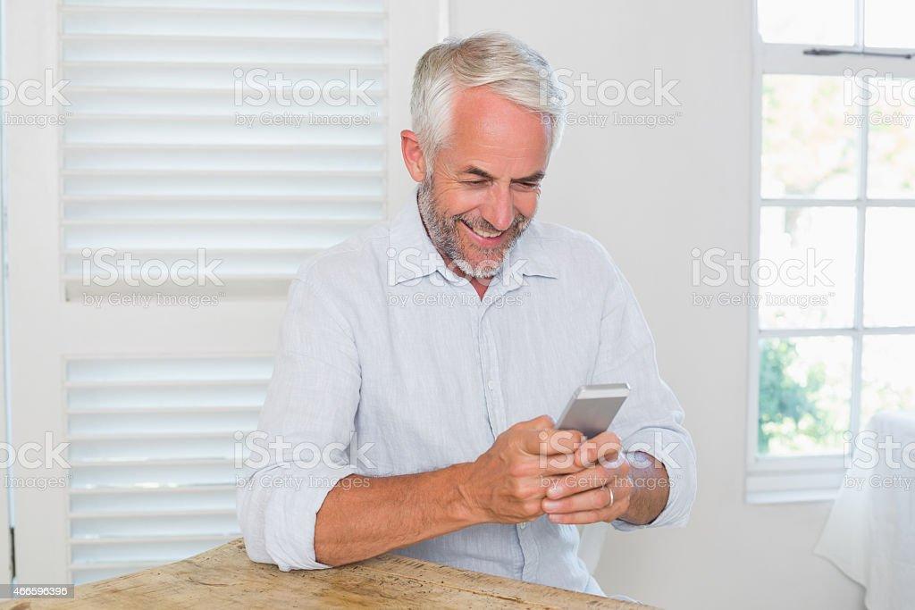 Mature man text messaging at home stock photo