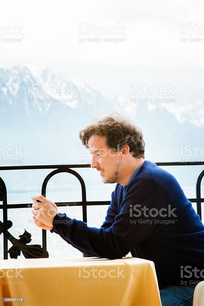 Mature man text messaging on balcony in Swiss Alps royalty-free stock photo