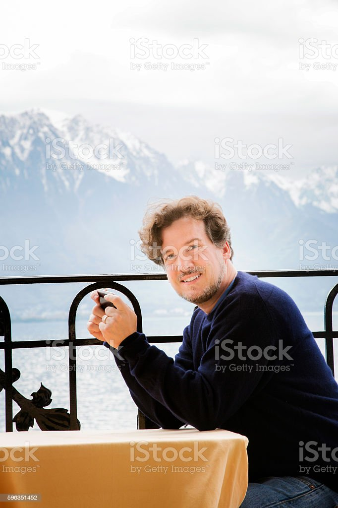 Mature man text messaging portrait on balcony in Swiss Alps royalty-free stock photo