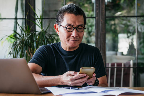Mature man texting on cell phone with paperwork and laptop stock photo