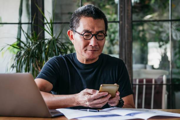 Reifer Mann SMS auf Handy mit Papierkram und laptop – Foto