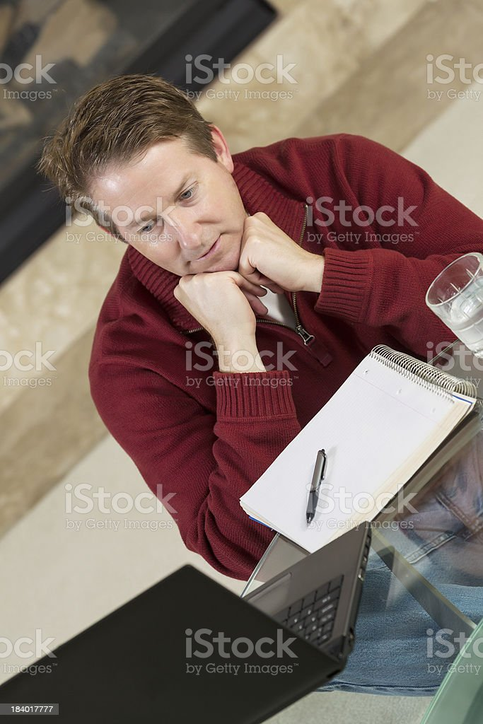 Mature man thinking while working from home royalty-free stock photo