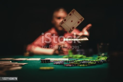One mature man playing poker late by night, throwing playing cards on table.