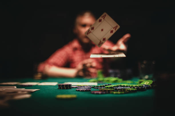 Mature man throwing playing cards on table stock photo