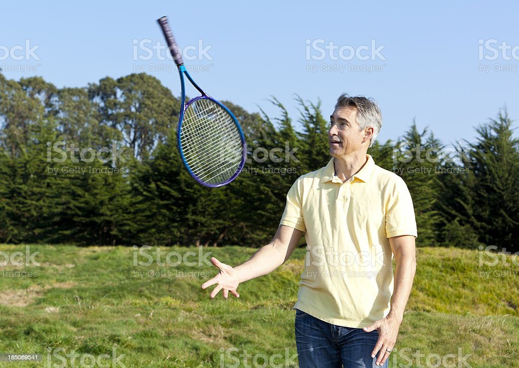 mature man throwing tennis racket in the air stock photo