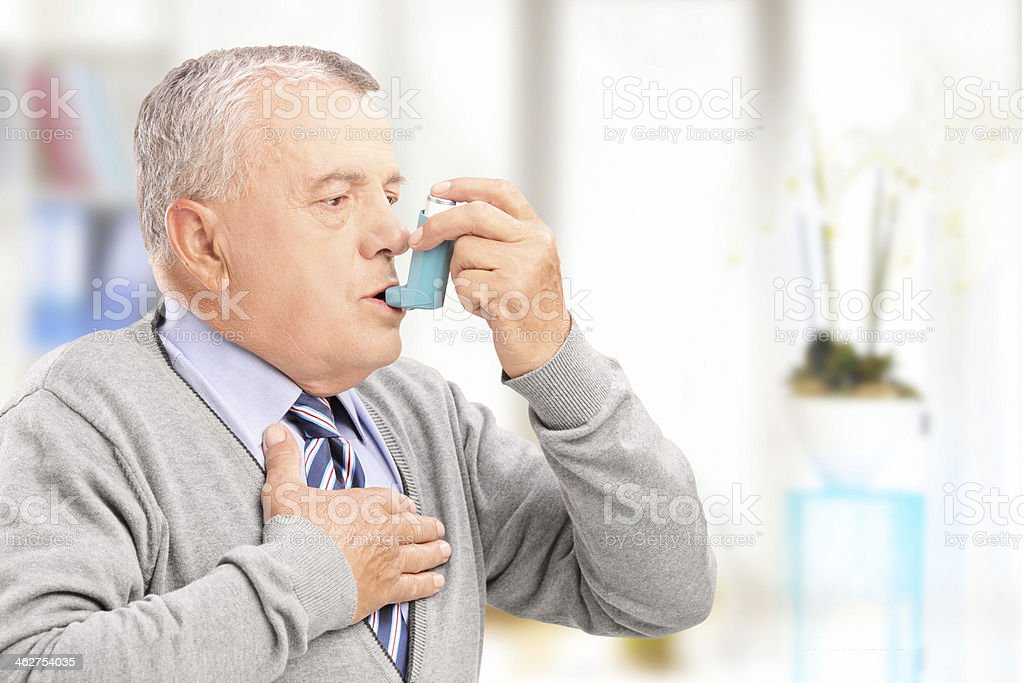 Mature man treating asthma with inhaler stock photo