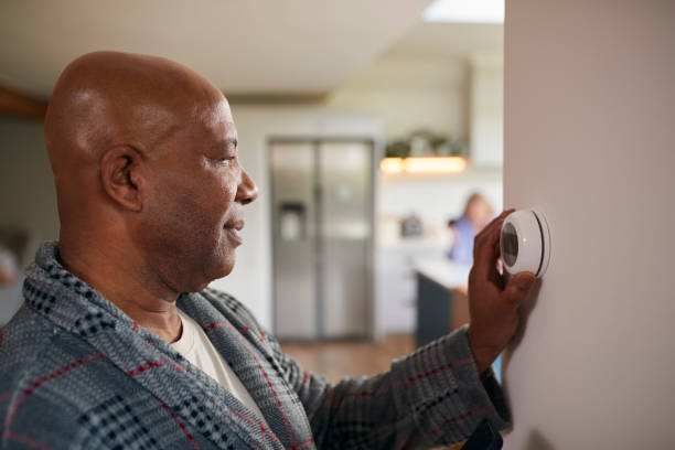 Mature Man Turning Control Dial On Digital Central Heating Thermostat At Home stock photo