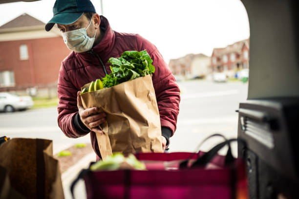 Mature man unloading grocery from car trunk stock photo