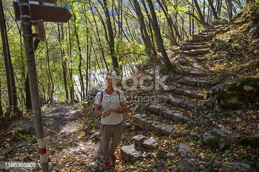 677206912 istock photo Mature man uses cell phone and trail sign for direction in forest 1165365903
