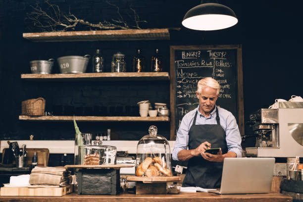 mature man using a calculator behind his cafe counter - small business owner stock pictures, royalty-free photos & images