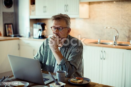 Close up of a mature man using a laptop at home while having breakfast