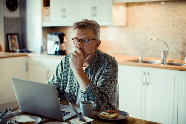 Mature man using a Laptop Close up of a mature man using a laptop at home while having breakfast worried stock pictures, royalty-free photos & images