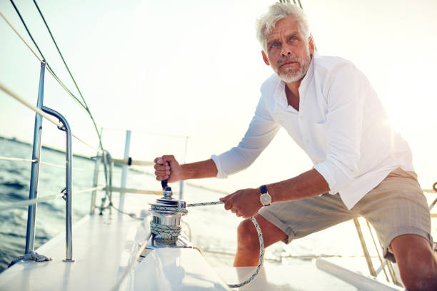 mature man using a winch while sailing on the ocean - cable winch stock photos and pictures
