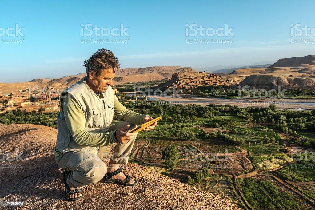 Mature Man Using Digital Tablet, Ait Benhaddou, Morocco, Africa stock photo