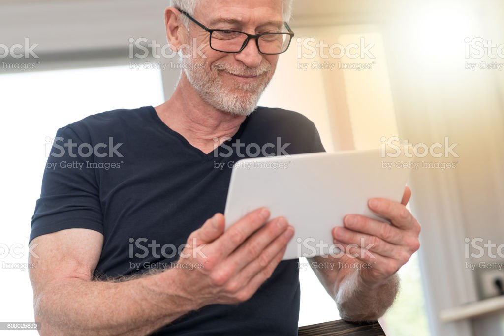 Mature man using digital tablet, light effect stock photo