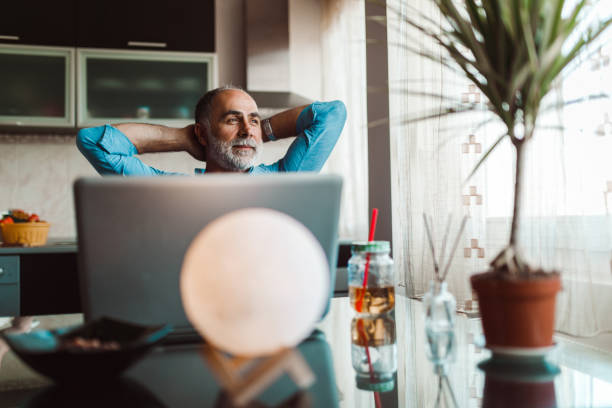 Mature man using laptop and working from home stock photo
