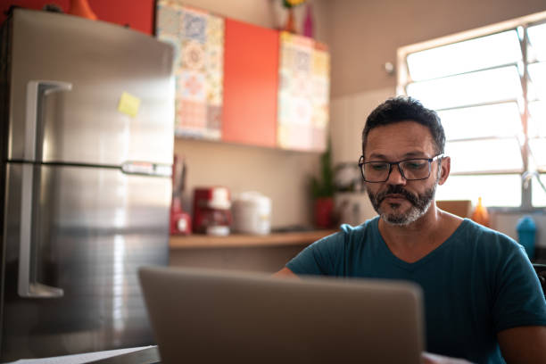 Mature man using laptop to work at home stock photo