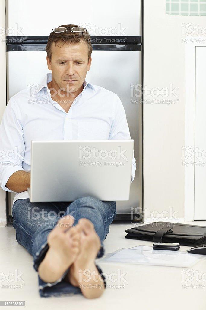 Mature man using laptop while sitting on floor royalty-free stock photo