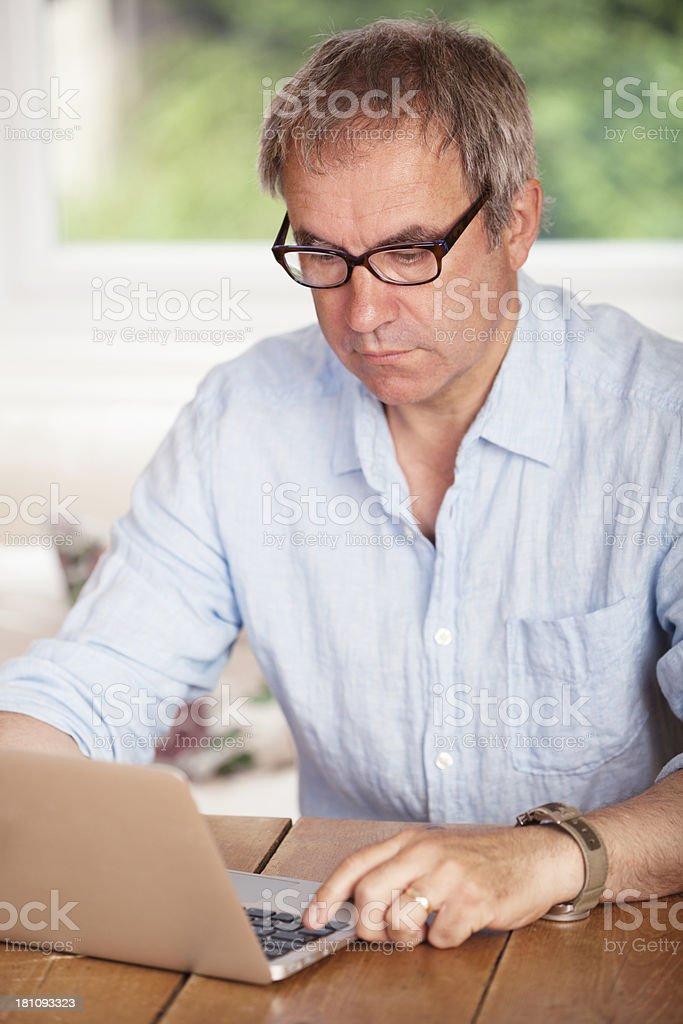 Mature man using laptop, working at home. royalty-free stock photo