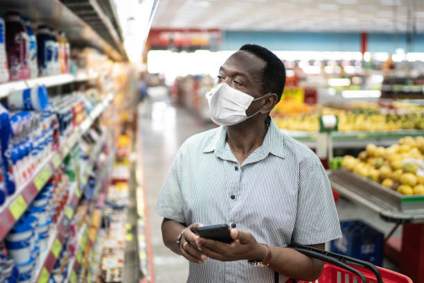 mature man using mobile and choosing products in supermarket - using face mask - afro latino mask imagens e fotografias de stock