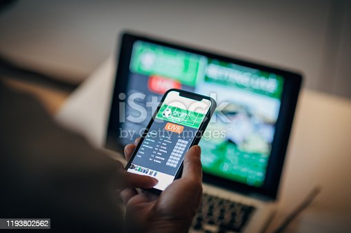Mature man using mobile app for live betting and online gambling and watching a sports match