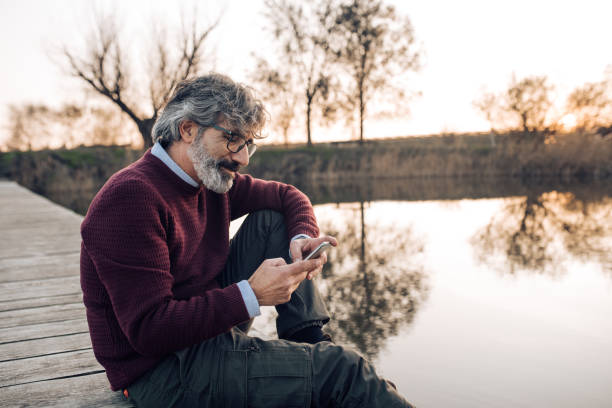 Mature man using phone and enjoying by the river stock photo