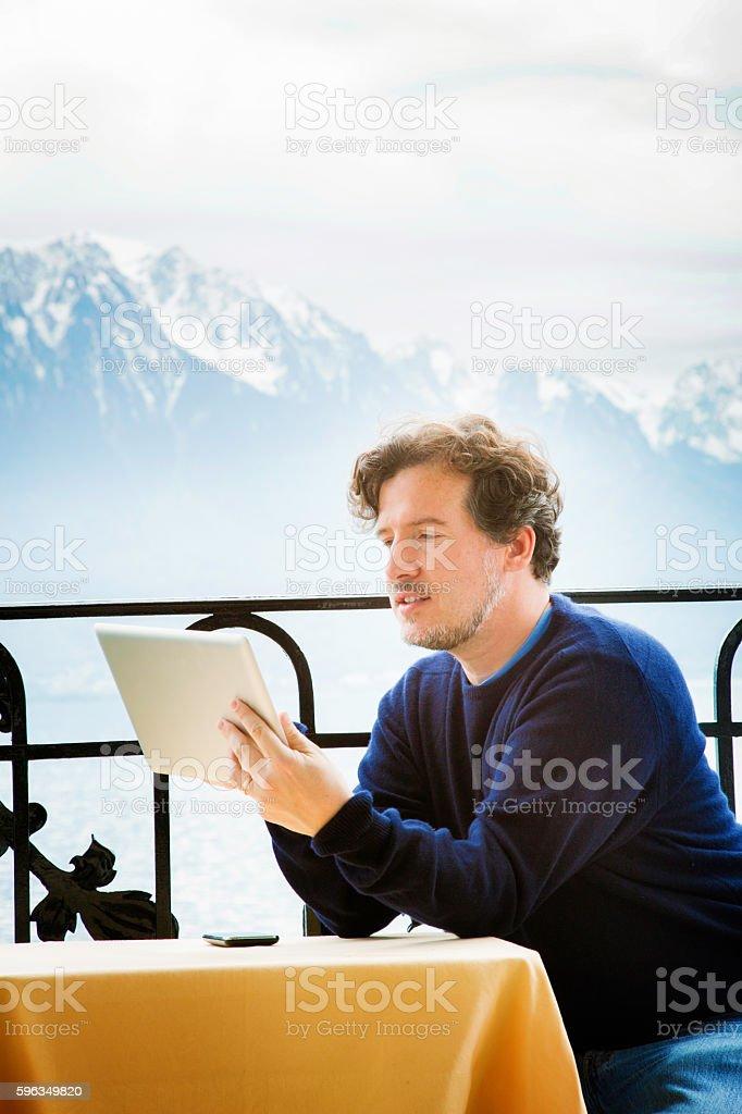 Mature man using tablet on balcony in Swiss Alps Lizenzfreies stock-foto