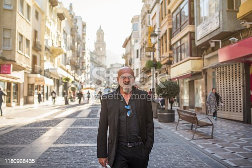 Mature man walking in street with suit in european city waling in sunny day
