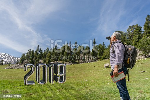 istock Mature man walking on top of the mountain in forest 2019 1053627286