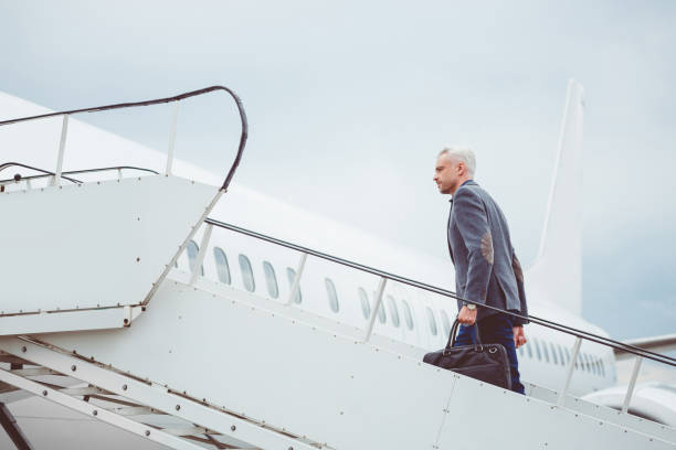 Mature man walking up stairs into airplane stock photo