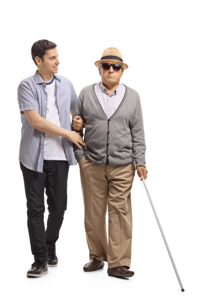 Mature man walking with the help of a young guy stock photo