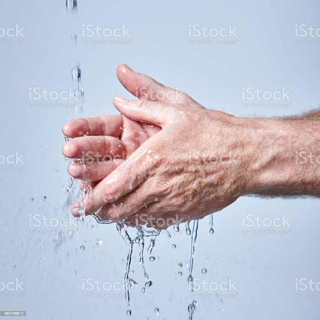 Mature man washes hands under running water royalty-free stock photo