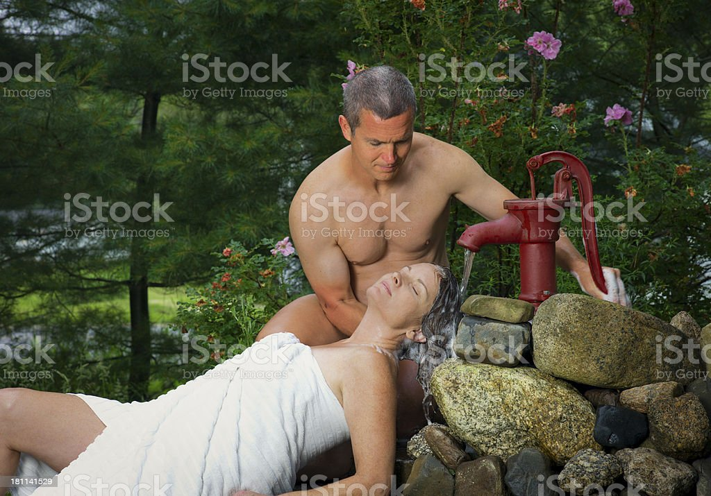 Mature Man Washes His Wife's Hair. stock photo