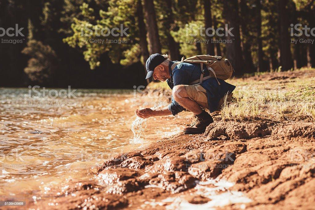 Mature man washing face from lake water stock photo