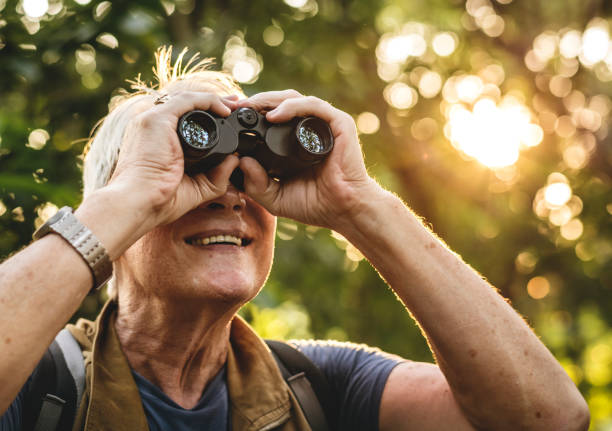 Mature man watching birds through binoculars stock photo