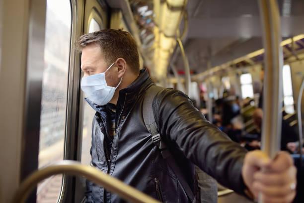 コロナウイルスの流行時にニューヨークの地下鉄の車の中で使い捨ての医療フェイスマスクを身に着けている成熟した男性。 - corona newyork ストックフォトと画像