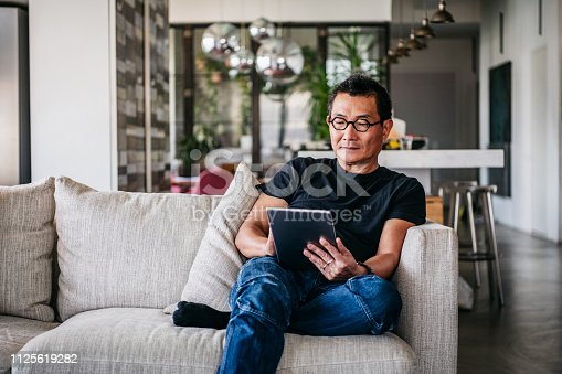 Chinese man in his 50s relaxing at home on sofa, casual clothes, reading ebook, surfing the internet