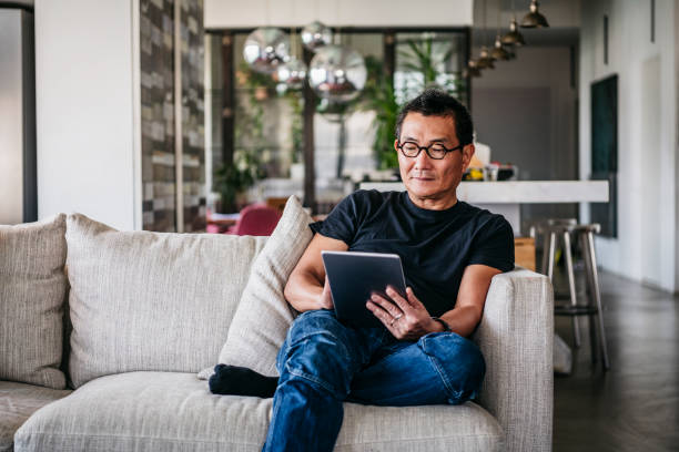 mature man wearing glasses using digital tablet - guy sofa foto e immagini stock