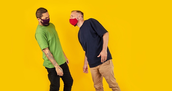 Mature man wearing mask while getting close to scared friend against yellow background
