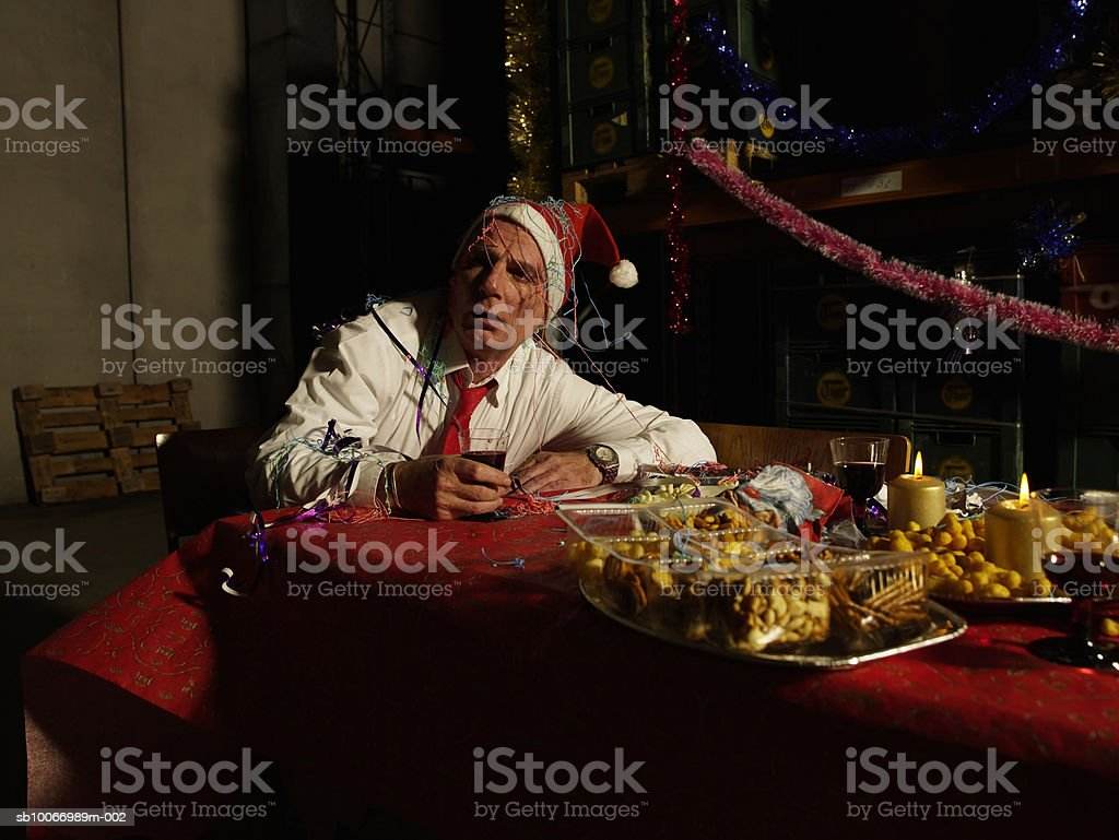 Mature man wearing santa hat, holding wine glass sitting at christmas table in warehouse royalty free stockfoto