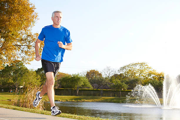 Mature man wearing shorts jogging past water fountain stock photo