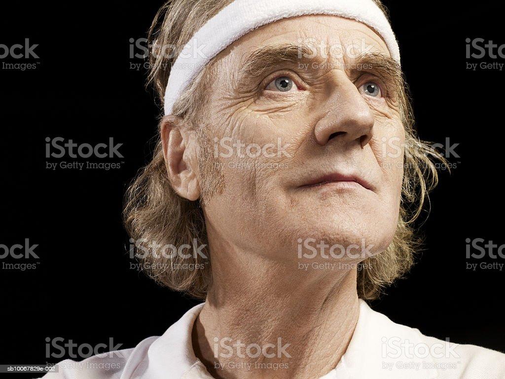 Mature man wearing sweat band on black background 免版稅 stock photo