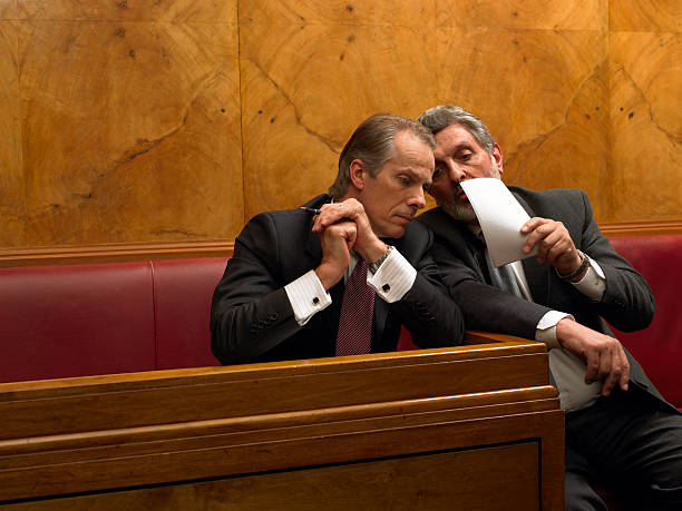 mature man whispering to colleague in pew - politician stock photos and pictures