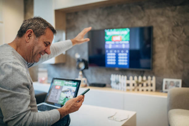 Mature man wins the online bet stock photo