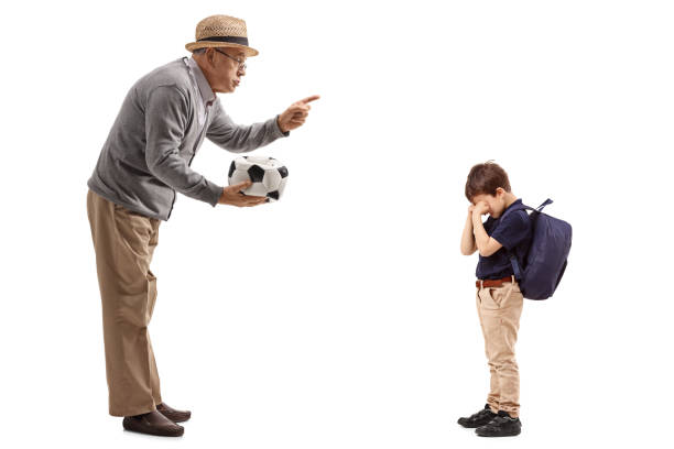 Hombre maduro con un balón de fútbol desinflado regañar a un niño - foto de stock
