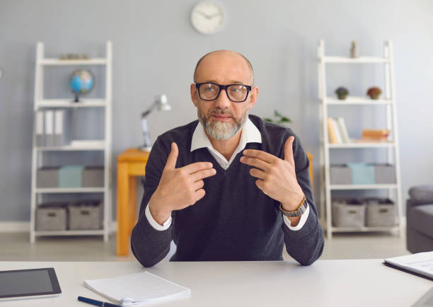Mature man with a gray beard looks at the camera, speaks with his partner sitting at a table in the office at home. stock photo